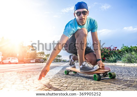 Cool skater doing a stunt on his skateboard - stock photo