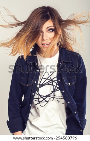 Cool smart teenager girl in jeans shirt with funny curious face and blowing hair - stock photo