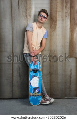 cool street skateboarder with sunglasses in front of iron wall.