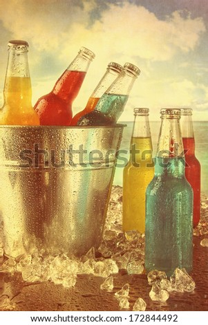 Cool summer drinks in ice bucket at the beach with vintage look - stock photo