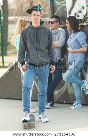 Cool teenage boy with skateboard in the skate park standing in front of his friends - stock photo