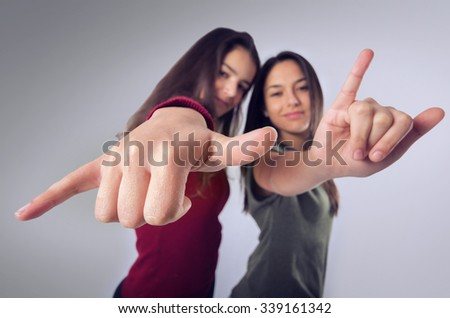 Cool teenager girl friends in happy expression doing hand signs - stock photo