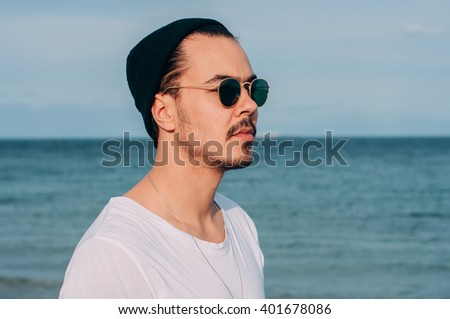 cool trendy stylish sexy handsome hipster lonely guy in sunglasses looking at the calm sea on the sunset. sunny summer day. tourist on vacation. close up portrait shot