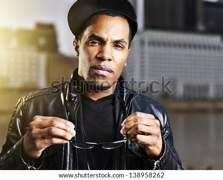 cool urban african american man  posing holding glasses - stock photo