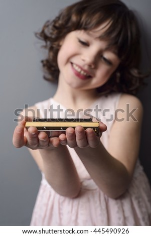 Cool wooden harmonica in the focus of the camera, the girl in the background is blurred. Little child looks with the pleasant smile on the musical instrument for playing blues.
