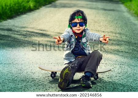 Cool 7 year old boy with his skateboard on the street. Childhood. Summertime. - stock photo