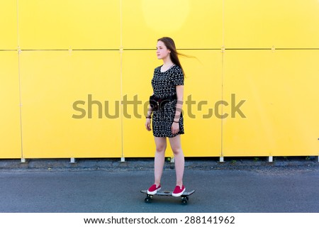 cool young and beautiful caucasian blonde teenager hipster skater girl with long gorgeous hair is having fun outside while skating with her cute little skate during amazing summer day - stock photo
