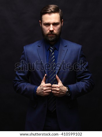 Cool young businessman standing on dark background - stock photo