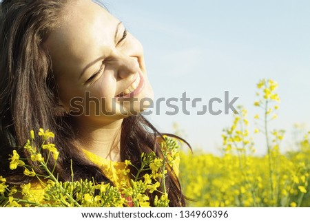 Cool young girl in the middle of a field of yellow flowers