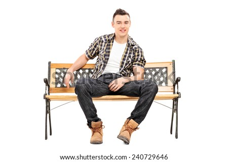 Cool young male model sitting on a bench isolated on white background - stock photo