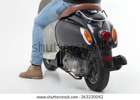 Cool young man is riding the scooter - stock photo