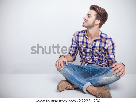Cool young man sitting a white table with his legs crosed looking away while smiling. - stock photo