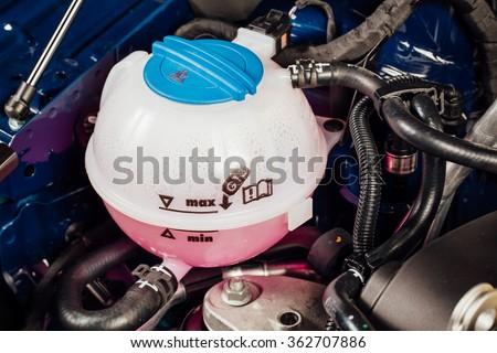 coolant antifreeze tank under engine hood - stock photo