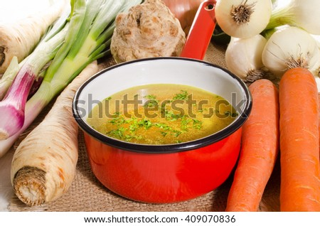 cooled vegetable stock in a red enamel pot - stock photo