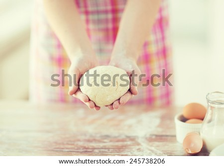cooling and home concept - close up of female hands holding bread dough - stock photo