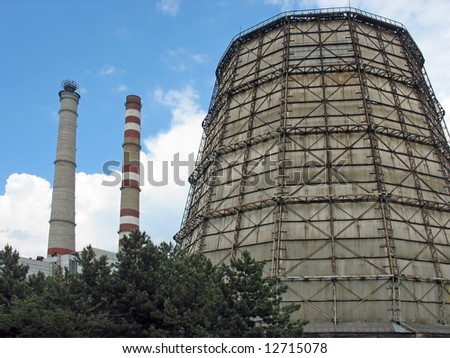 Cooling tower and two chimneys of a power plant - stock photo
