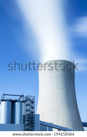 cooling tower from a lignite-fired power plant with steam on blue sky - stock photo