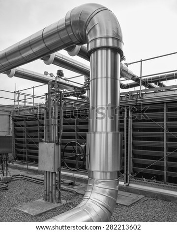 Cooling tower header pipe and valve.  Electrical conduits and mechanical system piping in a cooling tower yard. - stock photo