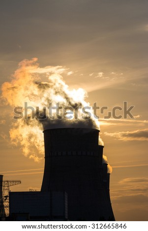 Cooling towers against sunset with electricity towers - stock photo
