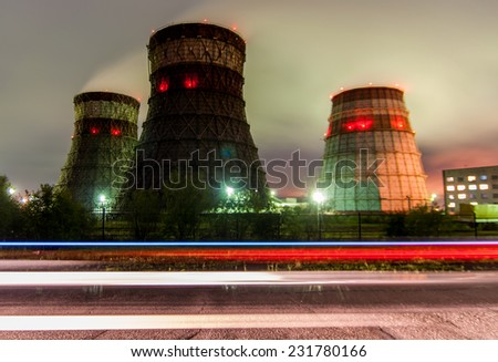 Cooling towers cogeneration - Khabarovsk, Russia in the foreground lights from a passing car - stock photo