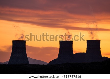 Cooling towers of nuclear power plant emitting steam during golden sunset - stock photo