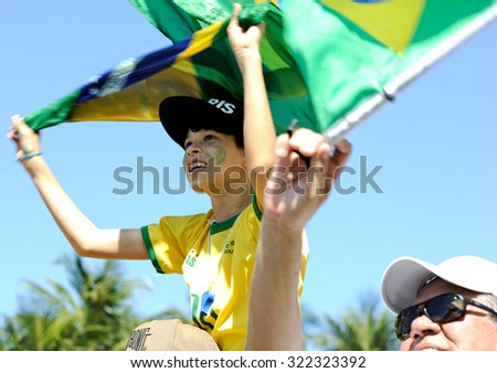Copacabana beach, Rio de Janeiro, Brazil - August 16, 2015: A boy waves a Brazilian national flag during a protest against President Dilma Rousseff.