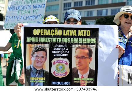 Copacabana beach, Rio de Janeiro, Brazil - August 16, 2015: A protester displays a banner supporting the Operation Car Wash, a police investigation into corruption at Petrobras. - stock photo