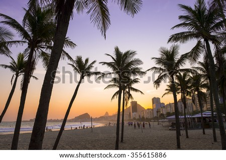 Copacabana Beach Rio de Janeiro view with palm tree silhouettes in front of colorful sunset sky from the Leme neighborhood - stock photo