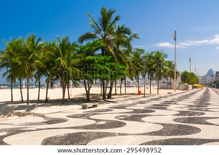 Copacabana with palms and mosaic of sidewalk in Rio de Janeiro. Brazil - stock photo