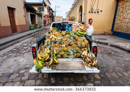 COPAN, HONDURAS, MAY 29, 2013: Unknown Honduran Farmer presenting his pineapple crops on a local market. - stock photo