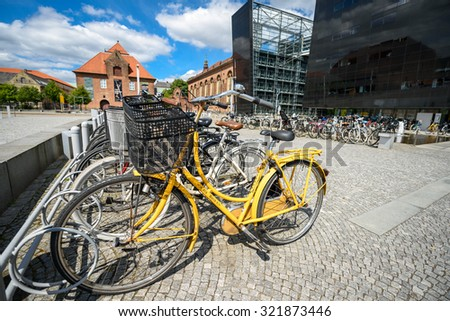 COPENHAGEN, DENMARK - AUGUST 01, 2015: Parked bicycles in the city. A lot of commuters, students and tourists prefer using bike instead of car or bus to move around the city. - stock photo