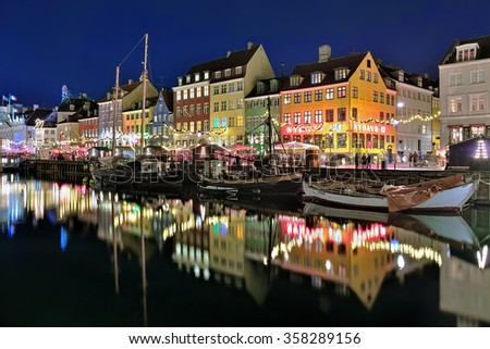 COPENHAGEN, DENMARK - DECEMBER 12, 2015: Evening view of Nyhavn. Nyhavn is a waterfront, canal and entertainment district with brightly colored 17th century townhouses and bars, cafes and restaurants. - stock photo