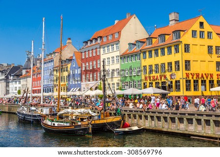COPENHAGEN, DENMARK - JULY 25: Nyhavn district is one of the most famous landmark in Copenhagen. People enjoy sunny weather in open cafees in Copenhagen on July 25, 2014 - stock photo
