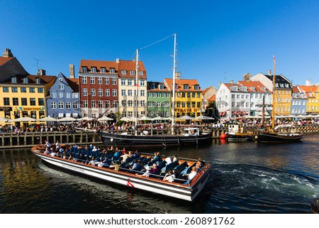 COPENHAGEN, DENMARK - JULY 9, 2014: Sunny weather welcomes tourists to the popular Nyhavn district in central Copenhagen as restaurants and bars prepare for the peak tourism season in Denmark.