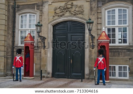 Copenhagen, Denmark - March 28, 2017: The guards of honor in red gala uniform guarding the Royal residence Amalienborg Palace in Copenhagen, Denmark
