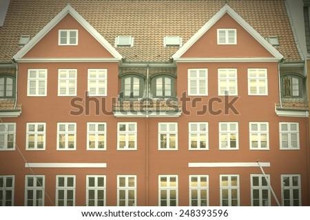 Copenhagen, Denmark - red building of Nyhavn street. Oresund region. Cross processed color tone - retro style filtered image. - stock photo