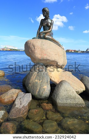 COPENHAGEN - JUNE 30: The Little Mermaid, a bronze statue by Edvard Eriksen, depicting a mermaid. The sculpture is displayed by the waterside at the Langelinie promenade in Copenhagen, Denmark  - stock photo