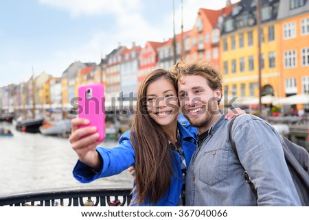 Copenhagen travel people taking friends selfie picture photos as souvenir with smartphone camera. Couple of tourists in the old port Nyhavn, famous Scandinavian attraction in Denmark, northern Europe.