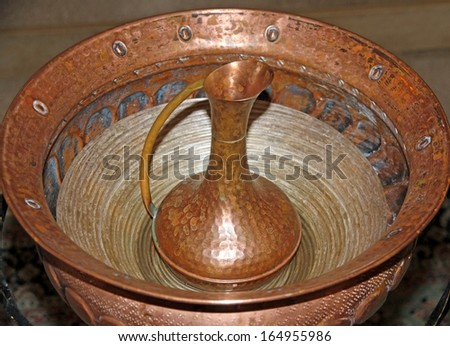 copper jug with the font for baptism of Christians - stock photo