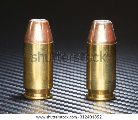 Copper plated bullets with hollow points on a cartridge for handguns - stock photo