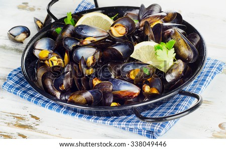 Copper pot of gourmet mussels  garnished with lemon slices. Selective focus - stock photo