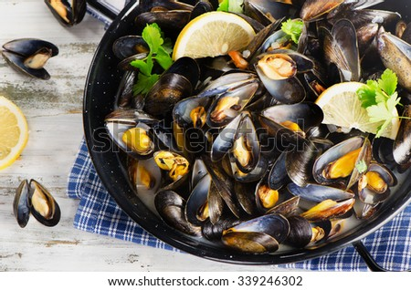 Copper pot of gourmet mussels served on a napkin garnished with lemon slices. Top view - stock photo