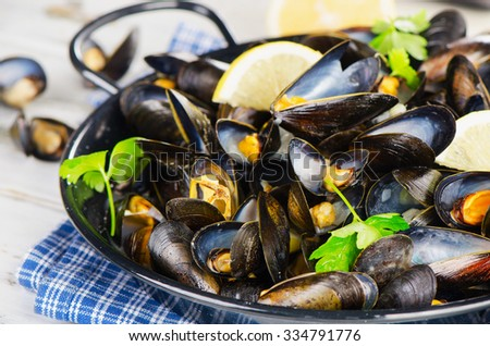 Copper pot of mussels garnished with lemon and herbs. Selective focus - stock photo