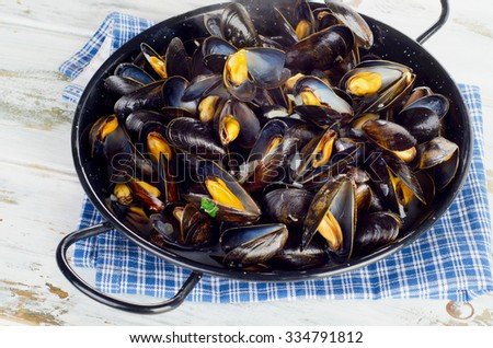 Copper pot of steamed mussels. Selective focus - stock photo
