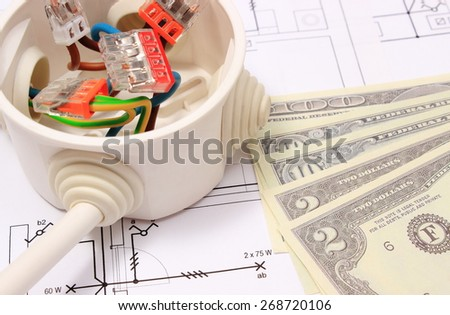 Copper wire connections in electrical box and money on construction drawing of house, concept for engineering and energy savings - stock photo