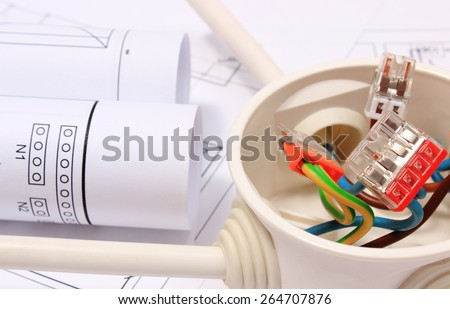 Copper wire connections in electrical box and rolls of electrical diagrams on construction drawing of house, accessories for engineering work, energy concept - stock photo