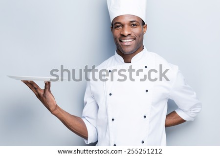 Copy space at his plate. Confident young African chef in white uniform holding empty plate and smiling while standing against grey background - stock photo