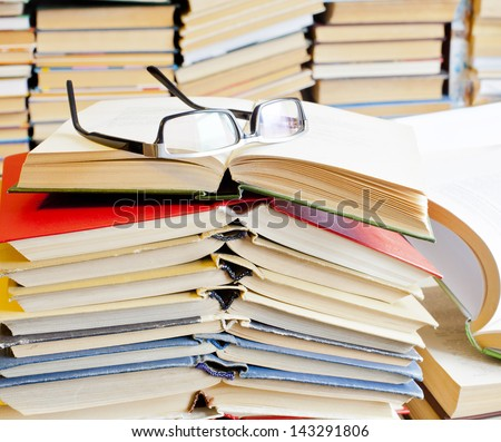 Copy Space for inscription opened books and glasses on table front of a full bookshelf - stock photo