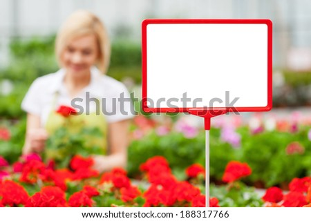 Copy space for your message. Close-up of copy space on the commercial sign with woman arranging flowers on the background - stock photo