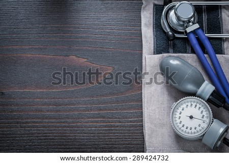 Copy space image of stethoscope and tonometer with pressure band on vintage wooden background medicine concept  - stock photo